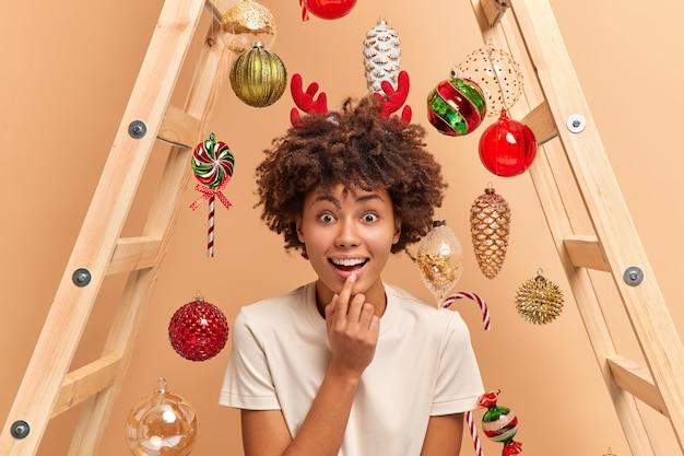 Alegre mujer de piel oscura mira fijamente con gran asombro centrado en la cámara abre la boca de interés mira el divertido programa de año nuevo en la televisión lleva poses de cuernos de reno