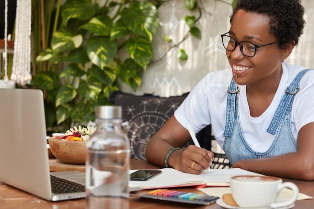 Alegre mujer de piel oscura mira seminario web en línea, enfocado en computadora portátil