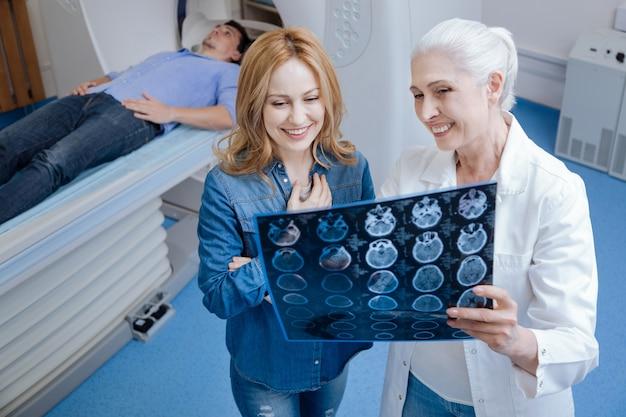 Alegre mujer positiva encantada de pie cerca del oncólogo y hablando con ella mientras mira la foto de rayos x