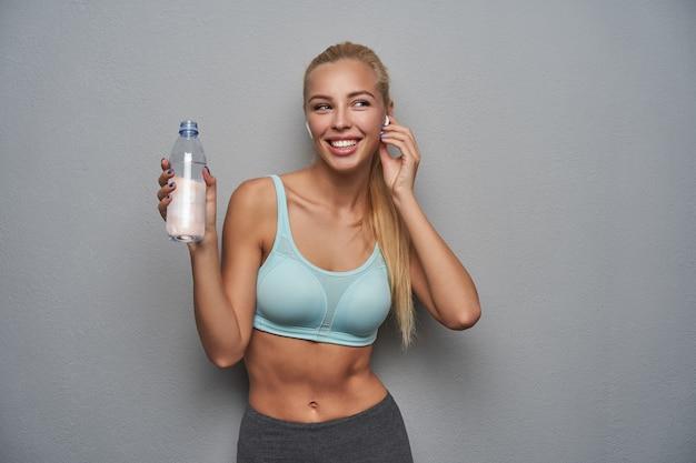 Alegre mujer rubia de pelo largo deportivo en buena forma física bebiendo agua después del entrenamiento y escuchando música con auriculares, con buen humor mientras está de pie aislado sobre fondo gris claro