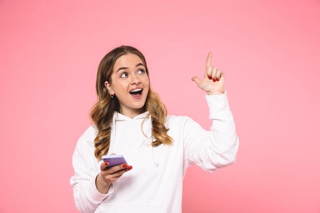 Alegre mujer rubia vestida con ropa casual apuntando a copyspace y mirando hacia arriba mientras sostiene el teléfono inteligente sobre la pared rosa
