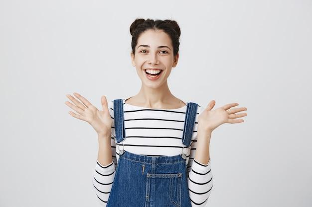 Alegre mujer sorprendida levanta las manos y sonriendo