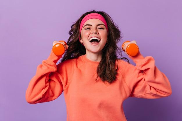 Alegre mujer en traje deportivo sosteniendo pesas
