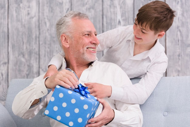 Alegre nieto y abuelo mirándose mientras sostiene la caja de regalo envuelta con lunares azules