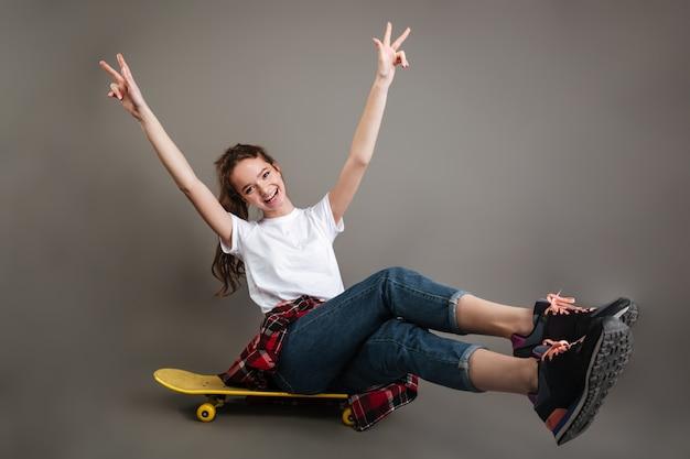 Alegre niña adolescente sentado en patineta y mostrando el signo de la paz