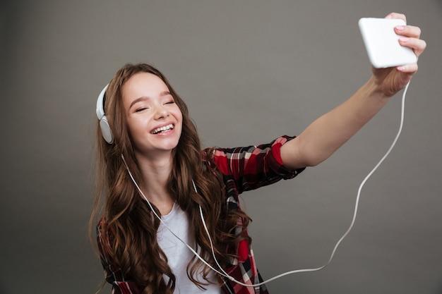 Alegre niña adolescente tomando selfie y escuchando música con auriculares