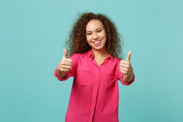 Alegre niña afroamericana en ropa casual mostrando los pulgares para arriba, mirando a cámara aislada sobre fondo de pared azul turquesa en estudio. personas sinceras emociones, concepto de estilo de vida. simulacros de espacio de copia.