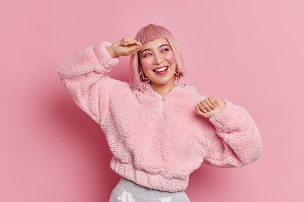 Alegre niña asiática expresa emociones sinceras, tiene cabello rosado baila con expresión feliz, se olvida de todos los problemas, tiene una vida despreocupada, usa maquillaje brillante, poses de abrigo de piel