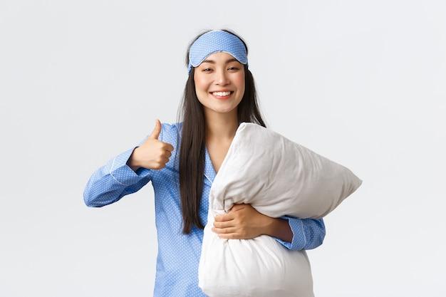 Alegre niña asiática linda complacida en pijama azul y máscara para dormir, sosteniendo una almohada suave y cómoda y mostrando el pulgar hacia arriba satisfecho, durmió bien por la noche, tomando pastillas para el insomnio.