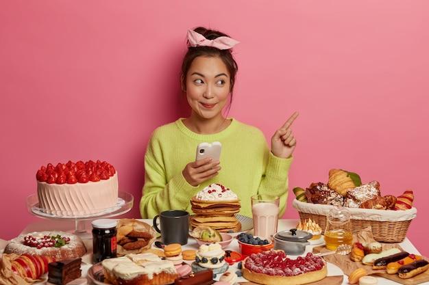 Alegre niña asiática morena alegre rodeada de galletas, galletas y pasteles, disfruta de la comida dulce durante el tiempo festivo, disfruta de las golosinas de las fiestas, señala el espacio en blanco, usa el teléfono móvil.
