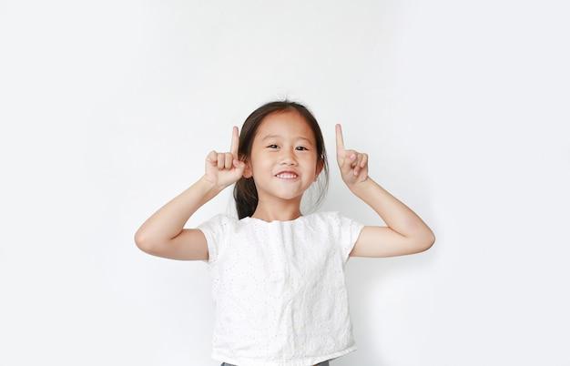 Alegre niña asiática niño levantó dos dedos índice para animar aislado