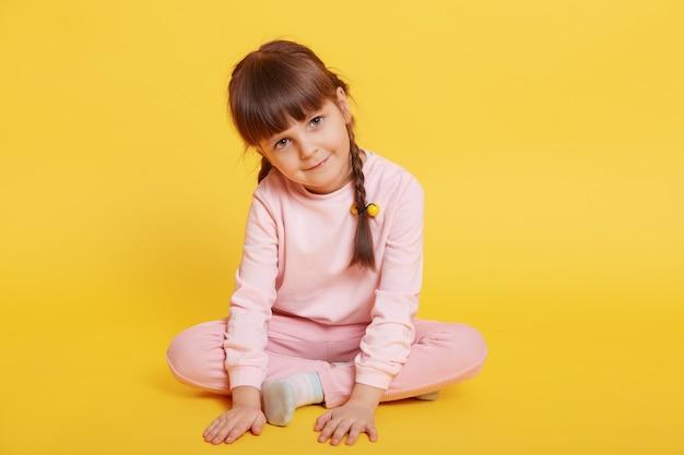 Alegre niña atractiva sentada en el piso con las piernas cruzadas, tocando el piso con las palmas, mirando a la cámara, posando aislada sobre fondo amarillo, viste atuendo rosa pálido.