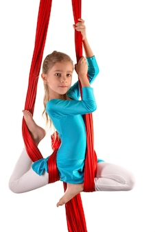 Alegre niña bonita en un traje de gimnasia azul hace trucos en una cinta de aire roja sobre un fondo blanco.