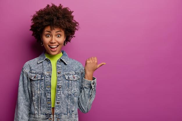 Alegre niña de cabello rizado señala con el pulgar hacia la derecha, muestra el área del espacio de la copia, se ríe positivamente, usa una chaqueta de mezclilla, aislada sobre una pared púrpura, demuestra un bonito anuncio contra la pared púrpura