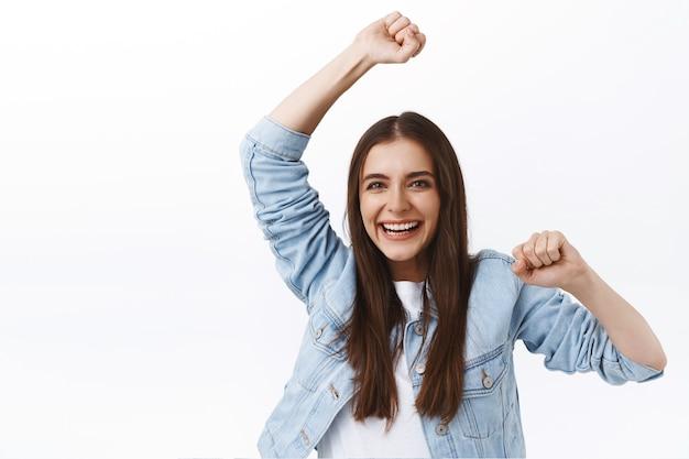 Alegre niña emocionada sonriendo felizmente, bailando triunfando como equipo ganador de la competencia, levantando la mano celebrando la victoria, apoyando a un amigo, riendo alegremente, animando sobre fondo blanco