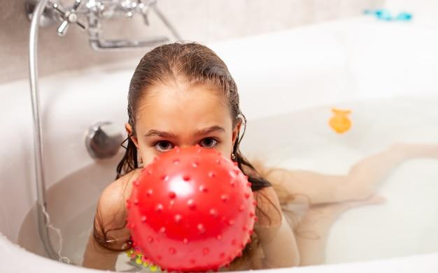 Alegre niña encantadora sonriente se baña con bola roja