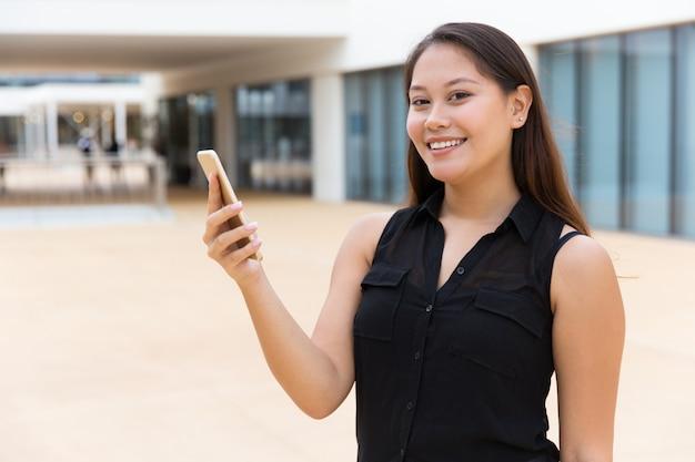 Alegre niña estudiante sonriente usando la aplicación en línea