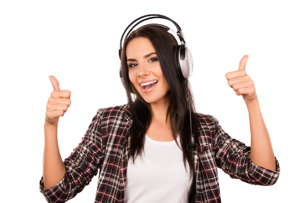 Alegre niña feliz escuchando música en auriculares y pulgares arriba