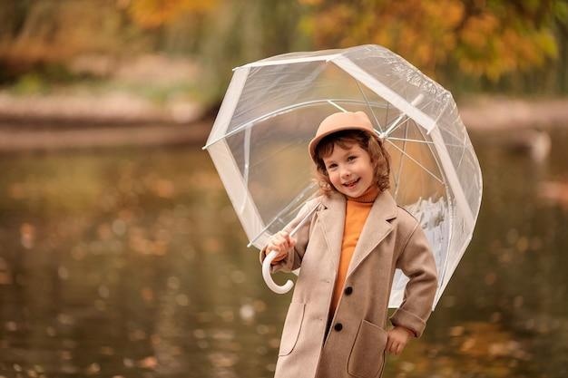 Alegre niña feliz con un paraguas transparente en un paseo en el otoño por el lago