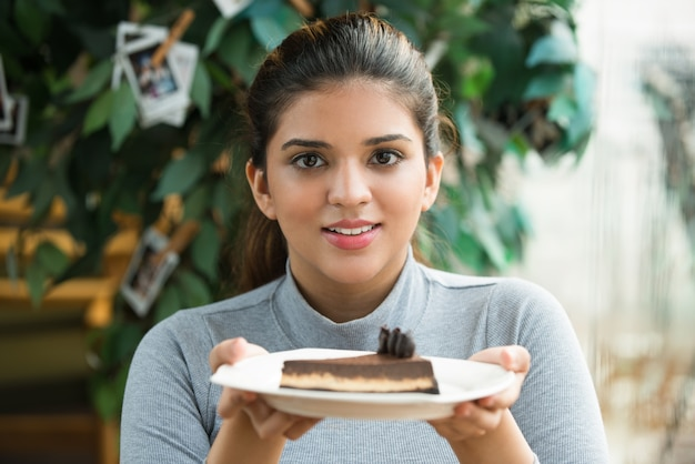 Alegre niña hermosa ha cocido pastel