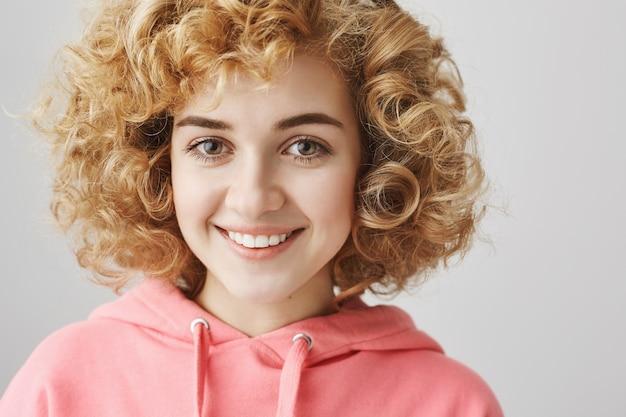 Alegre niña de pelo rizado sonriendo, radiante de felicidad