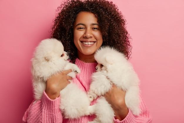Alegre niña de piel oscura descansa con dos perros en casa, lleva dos cachorros esponjosos de raza spitz