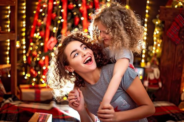 Alegre niña rizada linda y su hermana mayor divirtiéndose, abrazando cerca de árbol de navidad en el interior.