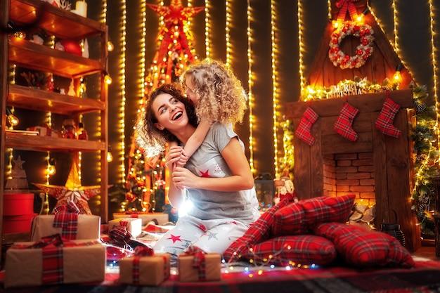 Alegre niña rizada linda y su hermana mayor intercambiando regalos.