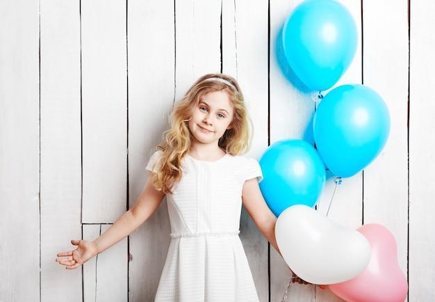 Alegre niña rubia con globos sobre fondo blanco de madera.