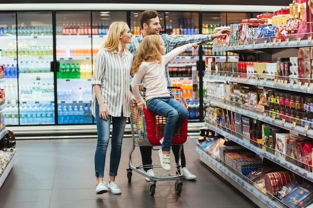Alegre niña sentada en un carrito de compras