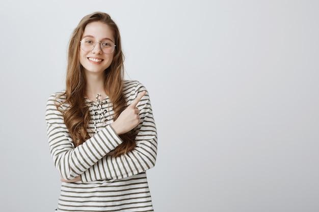 Alegre niña universitaria inteligente sonriente en vasos señalando el dedo en la esquina superior derecha