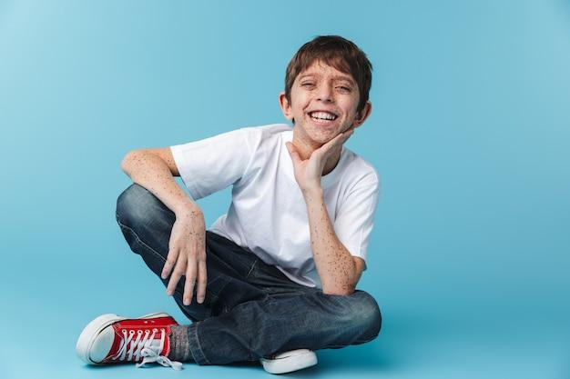 Alegre niño morena con pecas vistiendo camiseta blanca casual sonriendo mientras está sentado en el piso aislado sobre la pared azul