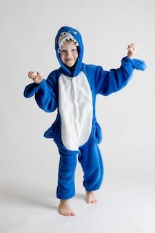Alegre niño posando sobre un fondo blanco en pijama kigurumi, traje de tiburón azul