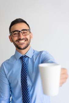 Alegre oficinista ofreciendo café