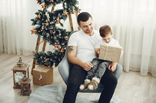 Alegre padre e hijo sentados cerca de decoraciones de navidad. el niño está sentado con alegría