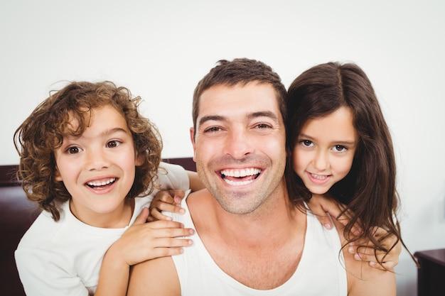 Alegre padre con hija e hijo en casa