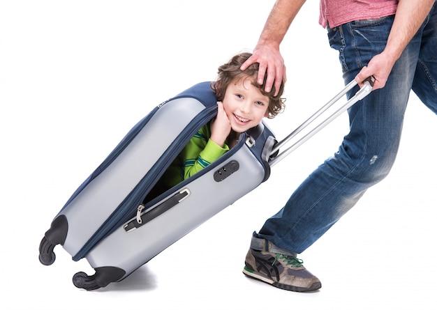 Alegre padre y su hijo en una maleta.