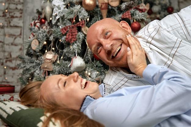 Alegre pareja abrazándose, disfrutando juntos en la víspera de navidad. concepto de navidad en previsión de un milagro, matrimonio familiar, joven pareja para el nuevo año.