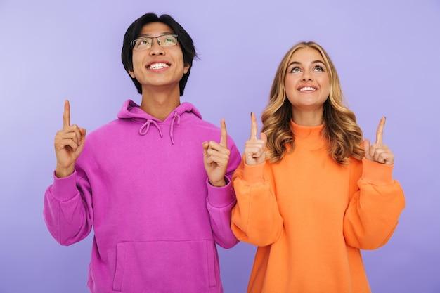 Alegre pareja de adolescentes multiétnicos de pie juntos aislados, apuntando hacia arriba