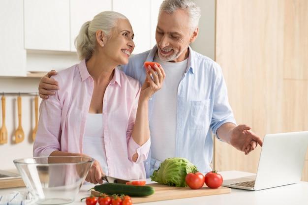 Alegre pareja amorosa madura familia usando laptop y cocina