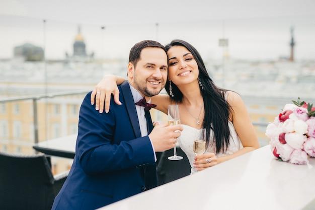La alegre pareja de casados se abrazan, tintinean copas con champán, tienen buen humor después de registrar su matrimonio