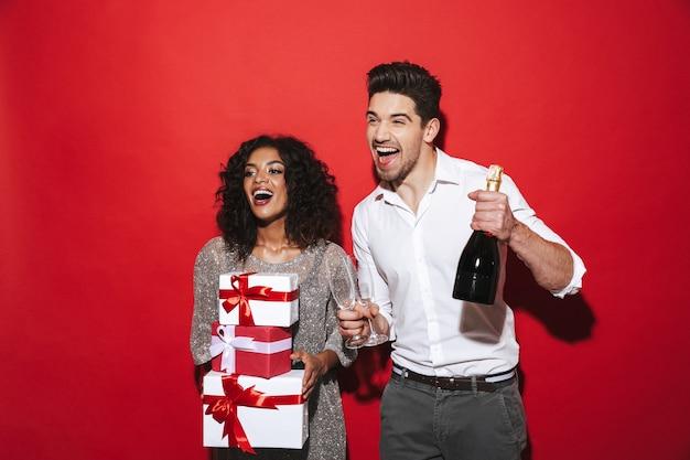 Alegre pareja elegantemente vestida que se encuentran aisladas sobre el espacio rojo, celebrando el año nuevo
