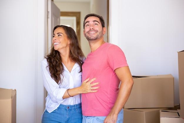 Alegre pareja emocionada mudarse a la nueva casa, de pie entre una caja de cartón, abrazándose y mirando a su alrededor