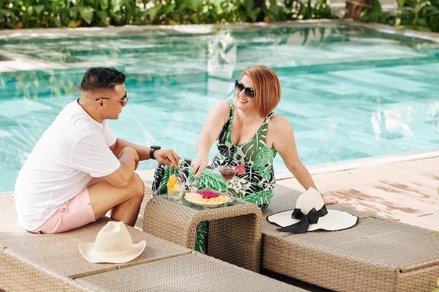 Alegre pareja de enamorados descansando junto a la piscina, comiendo frutas cortadas y bebiendo cócteles