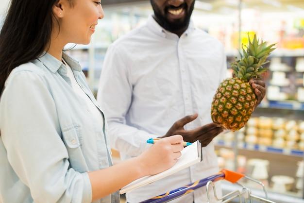 Alegre pareja multiétnica comprando productos en supermercado