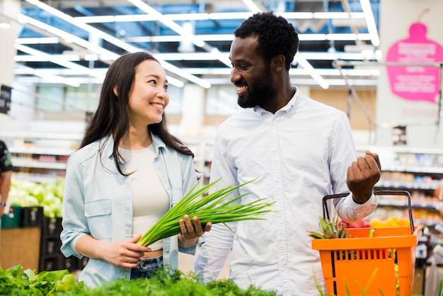 Alegre pareja multiétnica en tienda de comestibles