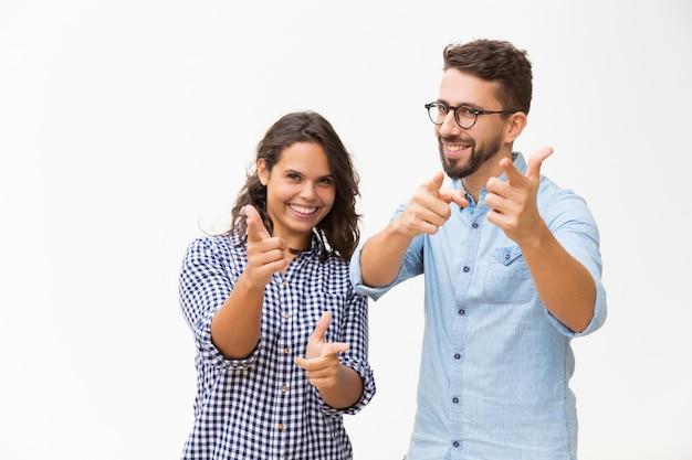 Alegre pareja positiva señalando con el dedo