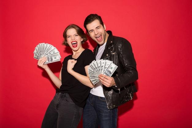 Alegre pareja punk gritando con dinero y mirando
