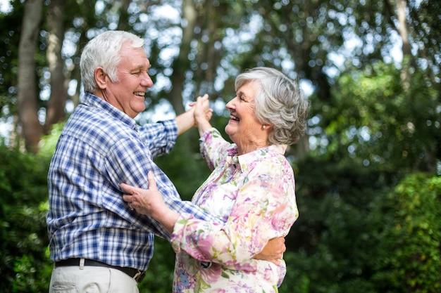 Alegre pareja senior bailando contra los árboles