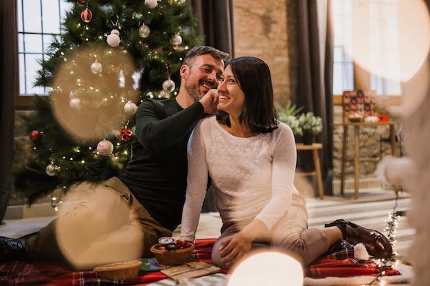 Alegre pareja senior con luces y árbol de navidad detrás